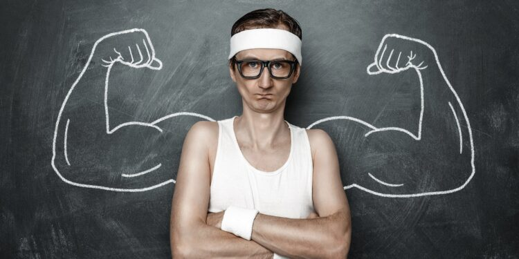 A picture of a skinny man in front of a blackboard with muscles drawn on him.