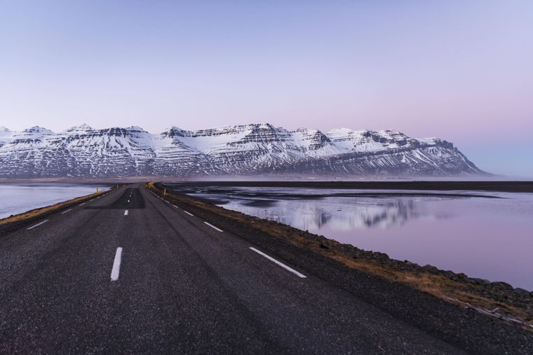 Rugged volcanic landscape and mountains with snow and sunset: Iceland's beauty can be seen along the Ringstrasse.