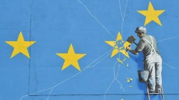 A mural painted by Banksy in the coastal city of Dover, UK, featuring the massive European Union flag and a carving worker star from the flag.  (Glenn Kirk / AFP)