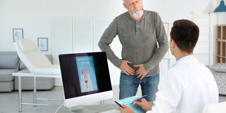 A man talks to a doctor while pressing on his lower back.