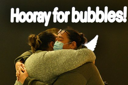 A woman (right) embraces a loved one before their departure for New Zealand at Sydney International Airport on April 19, 2021, when Australia and New Zealand opened a quarantine-free travel bubble through Tasmania.  (Photo by Saeed Khan / AFP)
