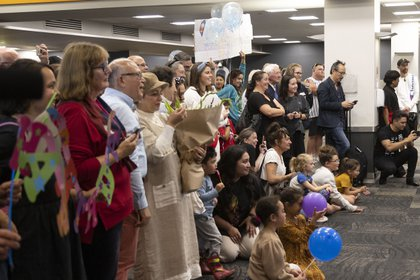 Families hope to be reunited when travelers on their maiden flight from Sydney arrive in Wellington on April 19, 2021, as Australia and New Zealand open a bubble of non-quarantine travel through Tasmania.  (Photo by Marty Melville / AFP)