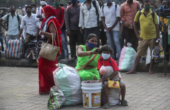 A woman and her children wait for a train at Lokmanya Tilak Station in Mumbai on April 11, 2021. India has reported an increase in Covid-19 infections, and new containment measures have begun.
