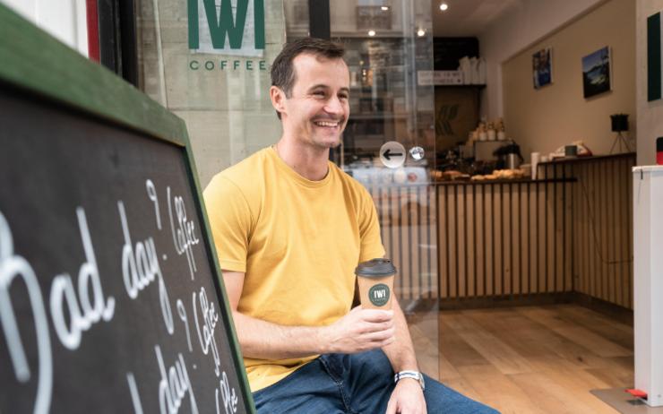 homme assis devant un café
