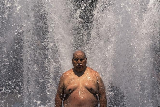 A man rests under a fountain in Portland, Oregon, June 27, 2021.