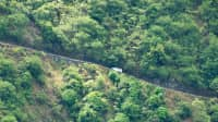 A white minibus drives on the Waipio Valley Road on the Big Island of Hawaii