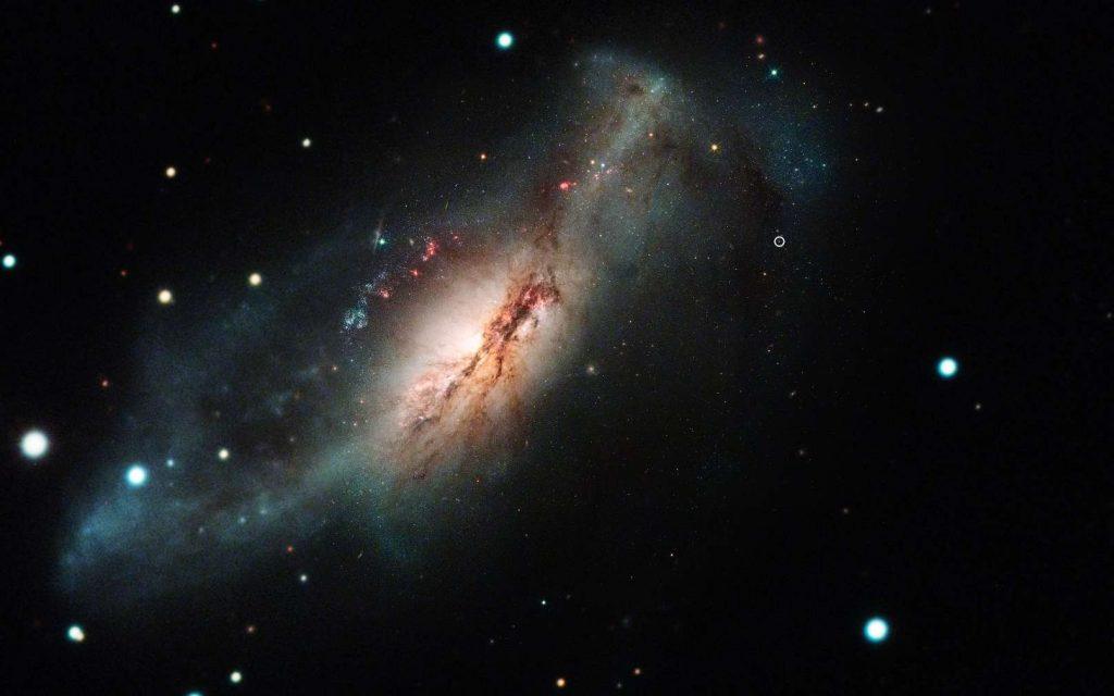 Une image composite formée de photos de l'observatoire de Las Cumbres et du télescope spatial Hubble montrant la supernova à capture d'électrons 2018zd (le cercle, en haut à droite) et sa galaxie hôte NGC 2146 (vers la gauche). © Nasa/STScI/J. DePasquale ; Observatoire de Las Cumbres