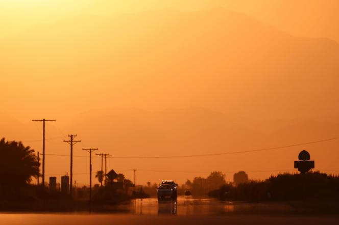 Cars seen through a mirage caused by high air temperatures, Thermal, California, July 10, 2021.