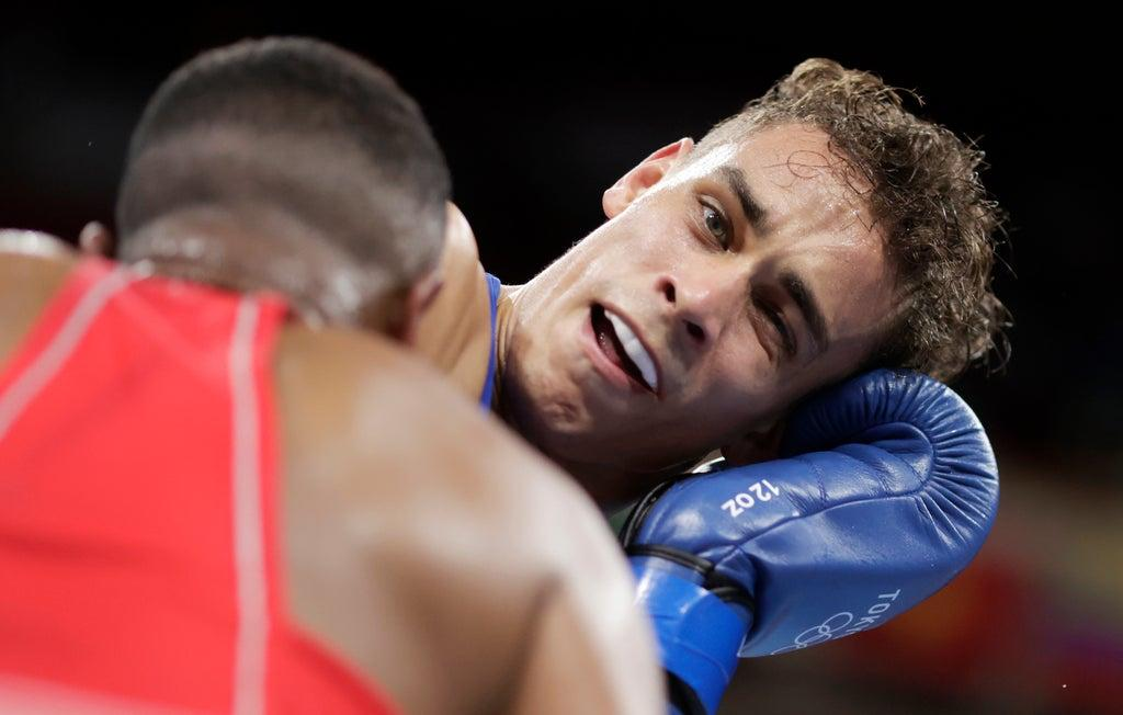 A Moroccan boxer tries to bite the ear of his New Zealand opponent