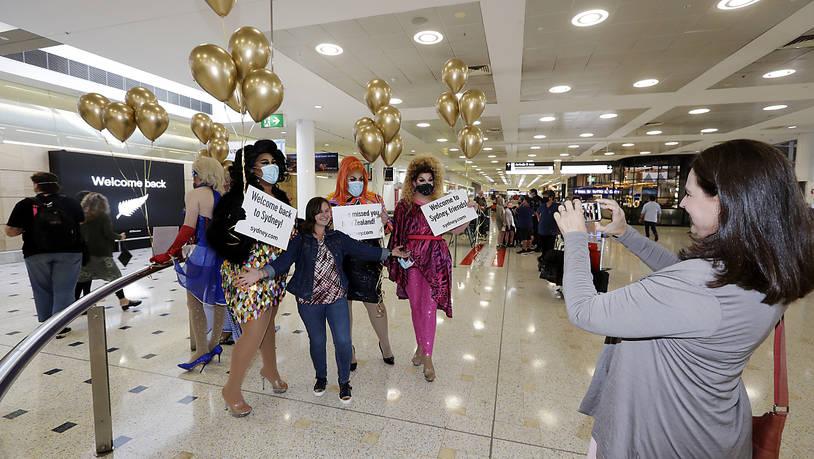 Eine Passagierin aus Neuseeland (M) stellt sich mit sich für ein Foto mit Drag Queens, die sie am Flughafen Sydney begrüßen, auf. Erstmals seit Beginn der Corona-Pandemie können Menschen in Neuseeland und Australien ab dem 19. April wieder zwischen…