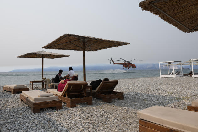 A firefighting helicopter fills water tanks along Pefki Beach on the island of Evia as vacationers watch on August 9, 2021.