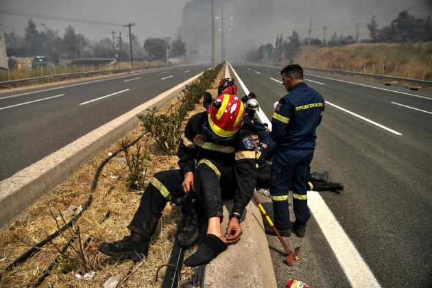 Firefighters take a break in Avidnes, north of Athens, on August 6, 2021.