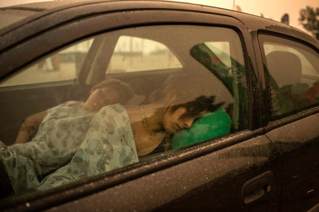Residents of Pefki, on the island of Evia, sleep in their car after they left their village under fire on August 8, 2021.