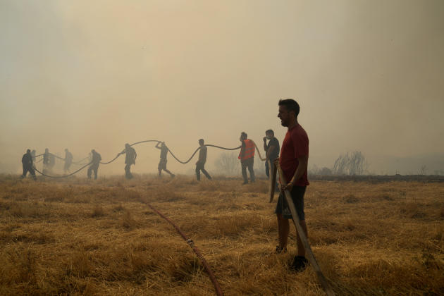 Villagers help firefighters carry water supply hoses to fight a fire, in Agios Stefanos, north of Athens, August 6, 2021.