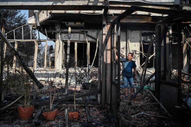 A man inspects the remains of his restaurant in Varybombi, a suburb of Athens, August 4, 2021.
