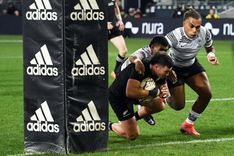 New Zealand midfielder David Haveli dives into the net to try despite a save by Fiji players during the test match, July 10, 2021 in Dunedin (New Zealand) (AFP - Harry Kurenga)