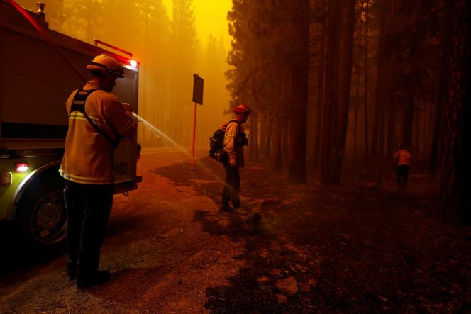 Firefighters extinguish flames at the Dixie Fire near Greenville Township, California, United States, August 6, 2021.