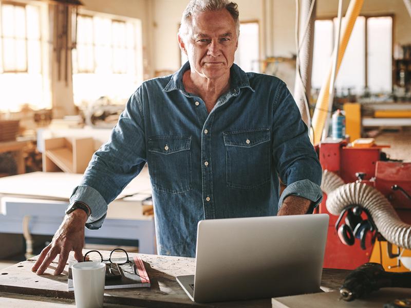 Menuisier se tenant debout dans son atelier, devant un ordinateur portable.