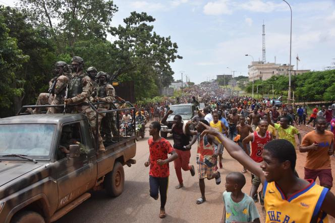 The crowd cheers the Guinean armed forces after the arrest of President Alpha Condé in Conakry on September 5, 2021.